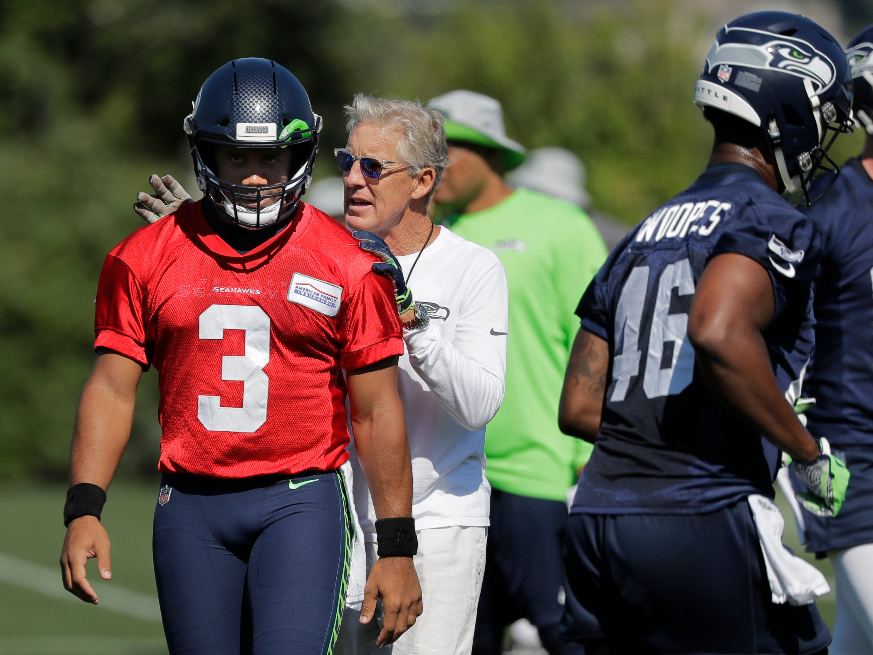 Seattle Seahawks head coach Pete Carroll, second from left, talks with quarterback Russell Wilson (3) during NFL football training camp, Thursday, July 26, 2018, in Renton, Wash. (AP Photo/Ted S. Warren)