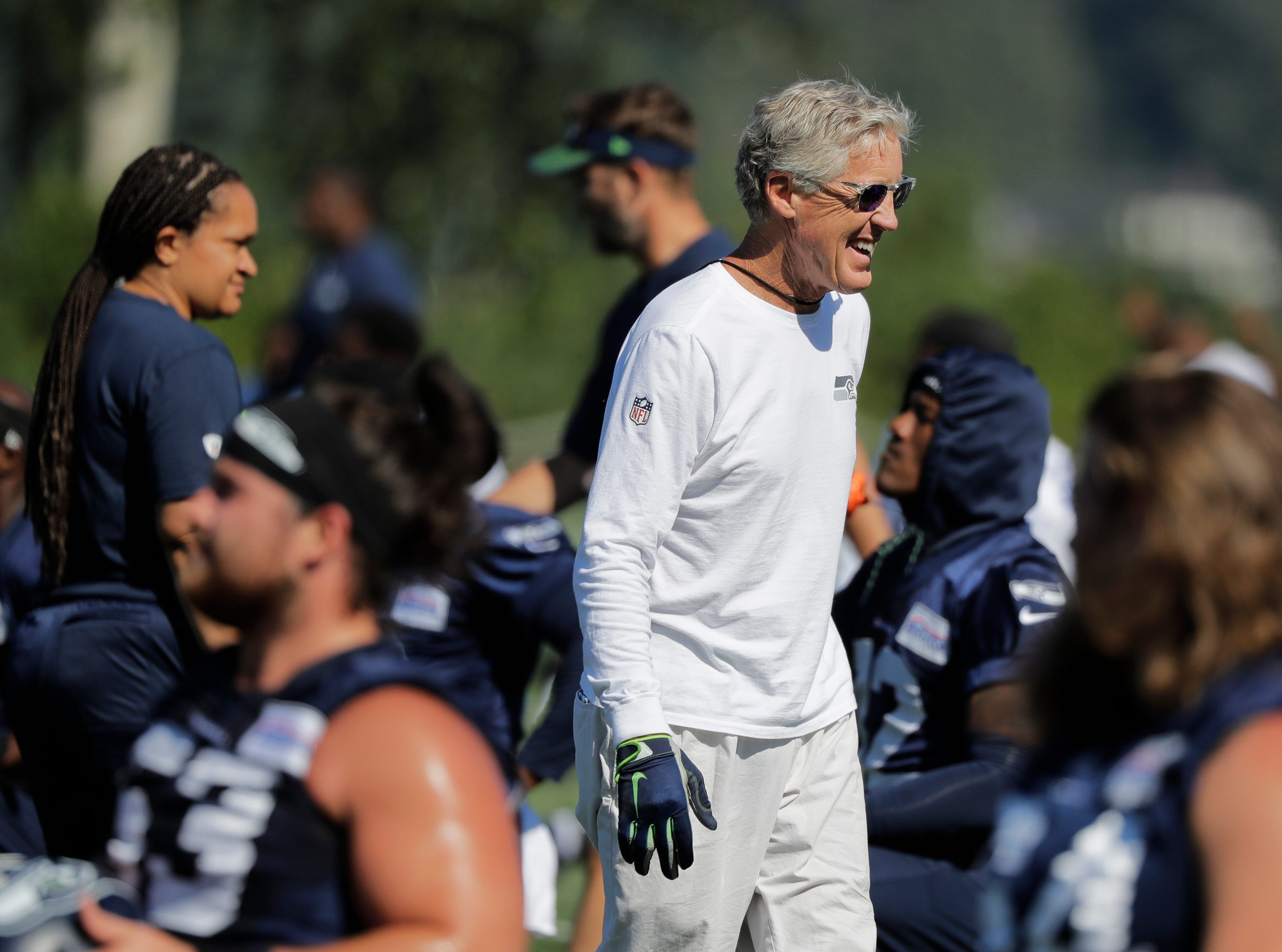 Seattle Seahawks head coach Pete Carroll smiles and he greets players at NFL football training camp, Thursday, July 26, 2018, in Renton, Wash. (AP Photo/Ted S. Warren)