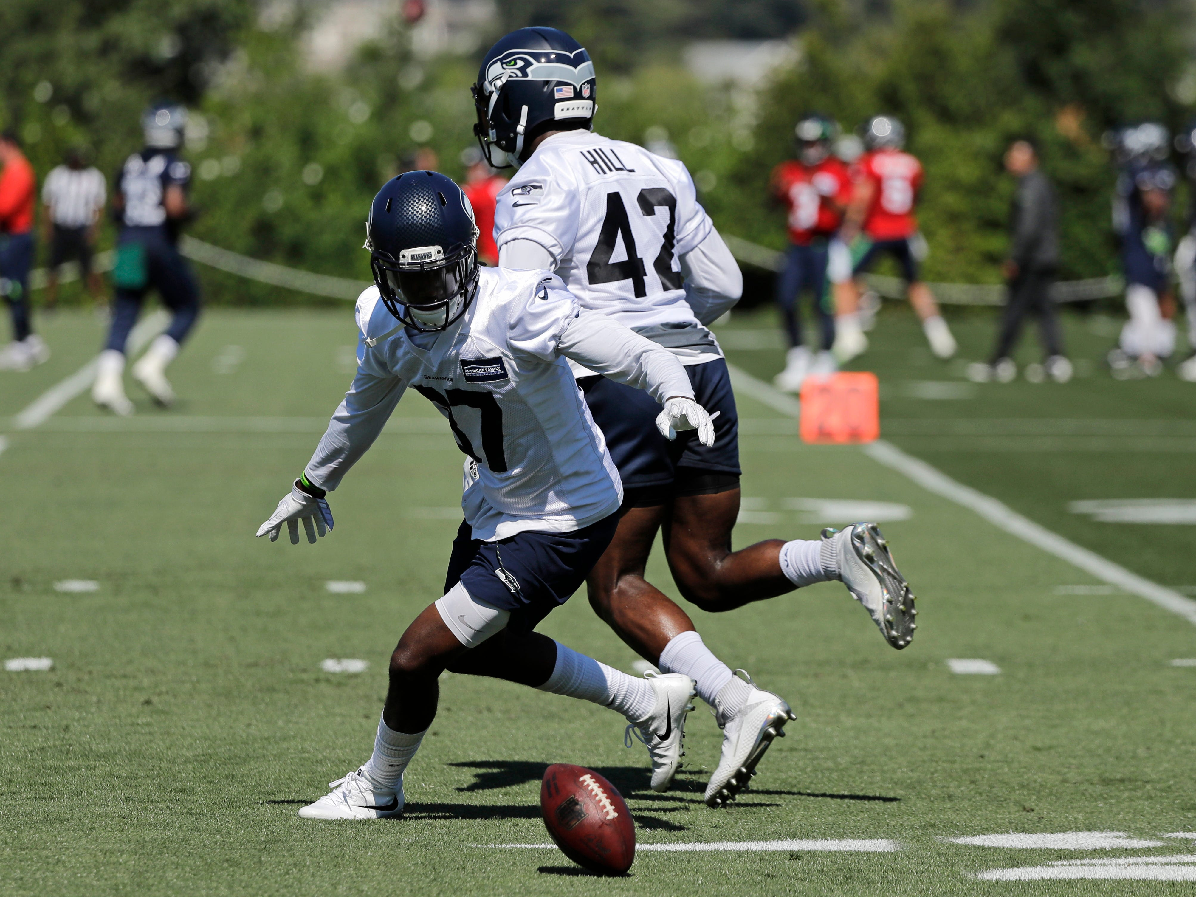 Seattle Seahawks cornerback Tre Flowers left, eyes the ball after he knocked it out of the hands of defensive back Delano Hill, right, during a drill at NFL football training camp, Thursday, July 26, 2018, in Renton, Wash. (AP Photo/Ted S. Warren)
