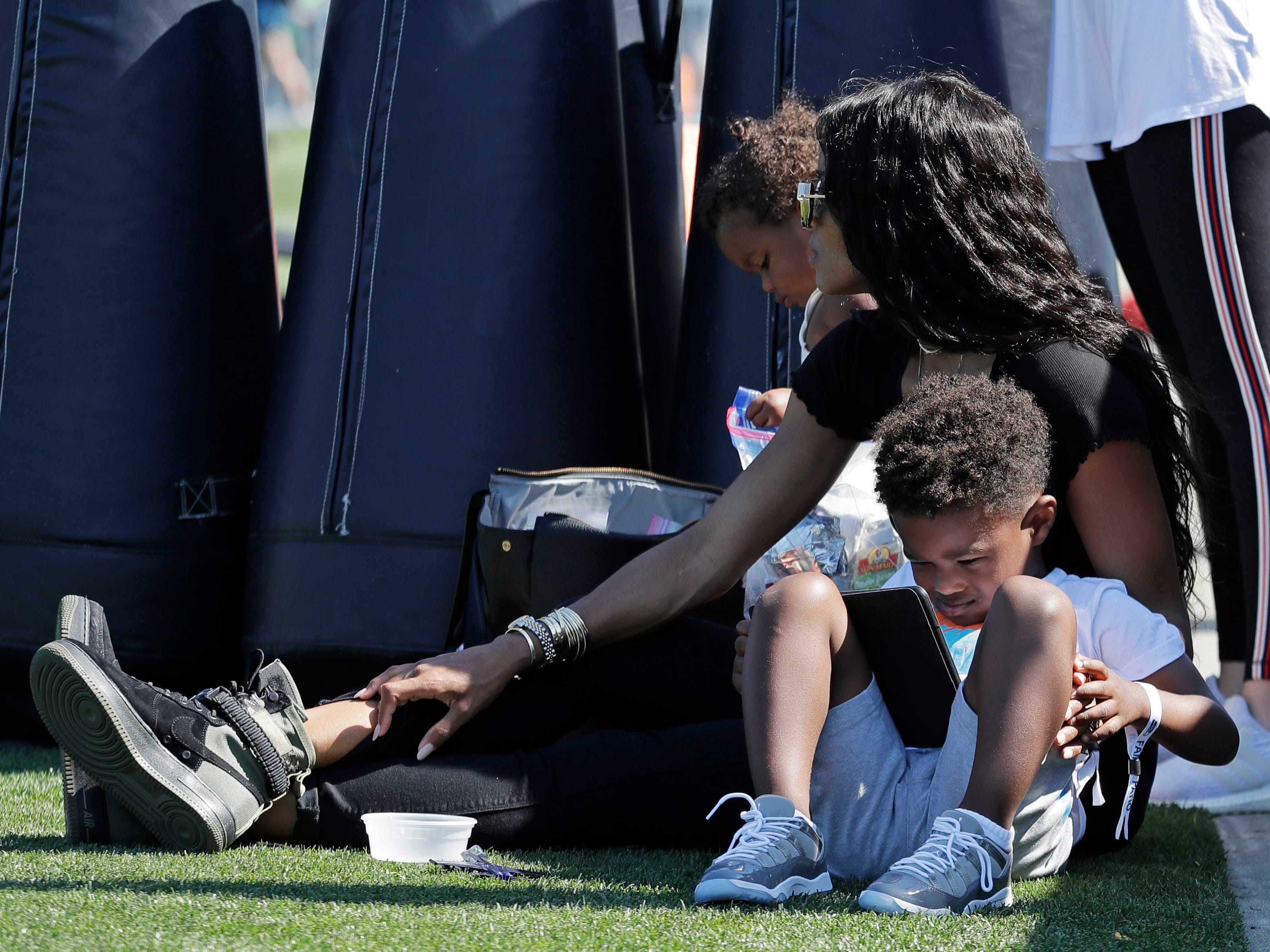 Pop singer Ciara, the wife of Seattle Seahawks quarterback Russell Wilson, sits with her children Sienna, left, and Future Zahir, right, as they watch the Seahawks' NFL football training camp, Thursday, July 26, 2018, in Renton, Wash. (AP Photo/Ted S. Warren)
