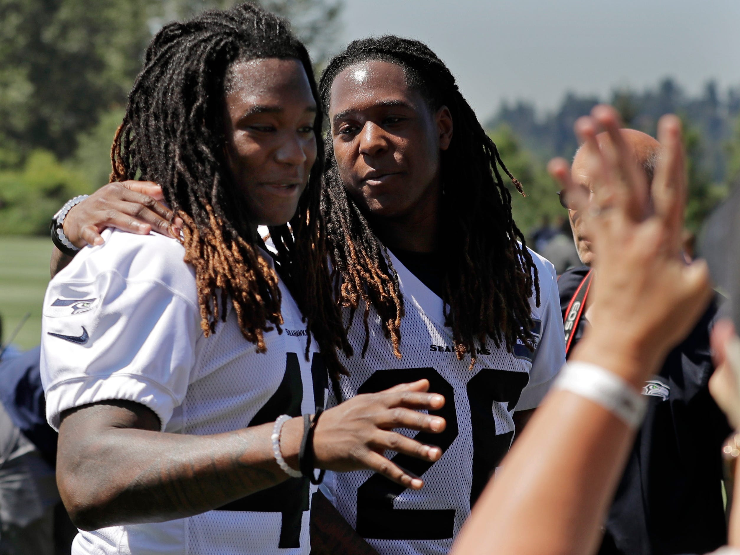 Seattle Seahawks' twin brothers, linebacker Shaquem Griffin, left, and cornerback Shaquill Griffin, greet fans after NFL football training camp, Thursday, July 26, 2018, in Renton, Wash. (AP Photo/Ted S. Warren)