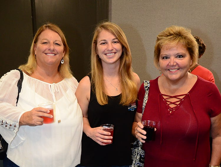 Men on Fire attendees Michelle Bayer, Brooke Bayer, and Lisa Cherland ready for the evening to start Saturday.