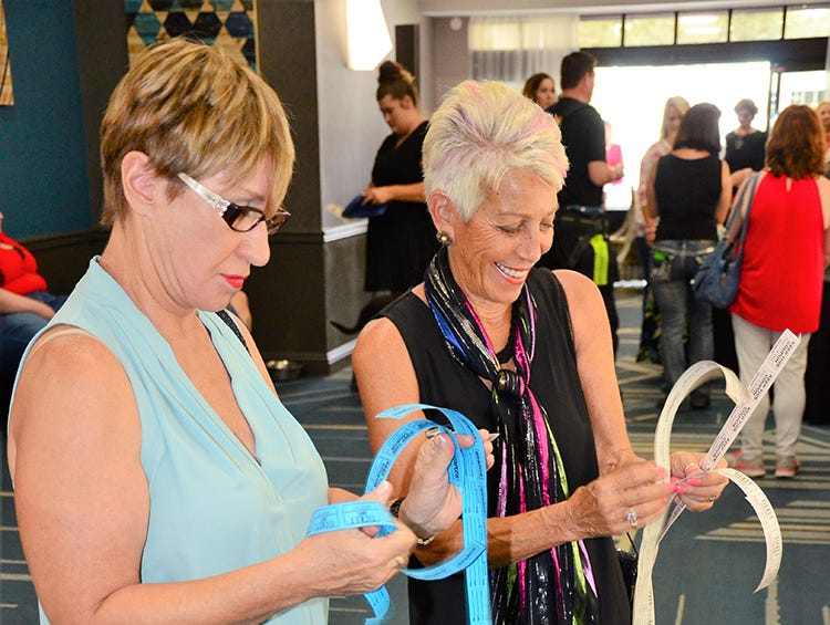 Judy Dassinger and Peri Kiros prepare to drop their tickets in hopes of winning some of the items up for auction Saturday night in Melbourne during the Men on Fire benefit for the SPCA. day)