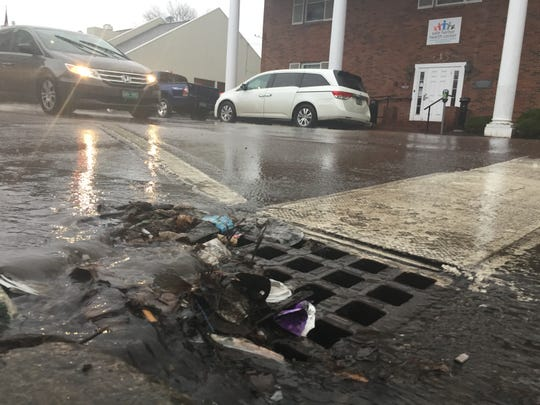 Stormwater and water-borne debris sluice into a drain on South Winooski Avenue at King Street in late May 2017.