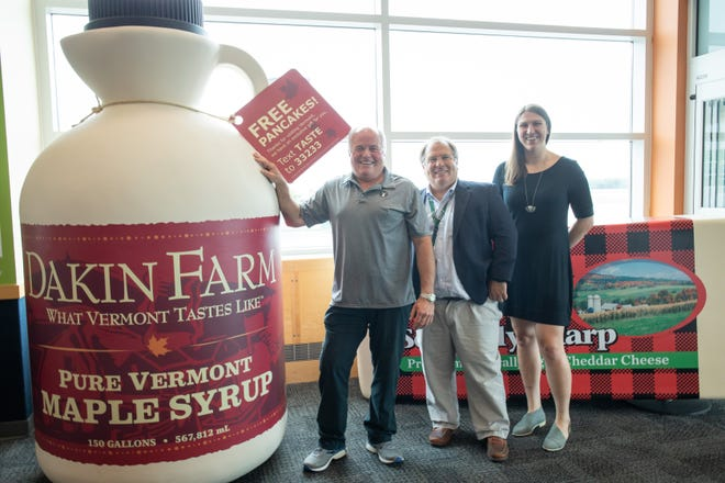 Sam Cutting IV, president and owner of Dakin Farm, Gene Richards, director of aviation at Burlington International Airport, Emily Lopuski, marketing manager at Dakin Farm, pose Thursday, July 26, 2018, with giant replicas of a maple syrup jug and a block of cheese.