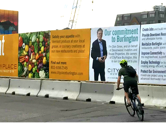 A cyclist pedals by a larger-than-life image of CityPlace developer Don Sinex posted at the perimeter of the construction site on Thursday, July 25, 2018.