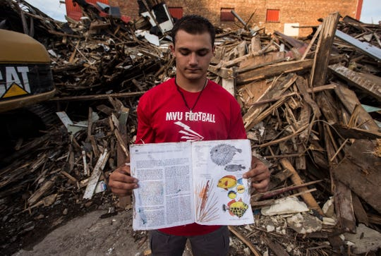 Hunter Nunes-Wales, a multi-sport Missisquoi star, pulls a coloring book from the rubble of his former home in Swanton, torn down earlier this summer. Hunter's biological father abused him and his siblings and the state stepped in and removed them all.