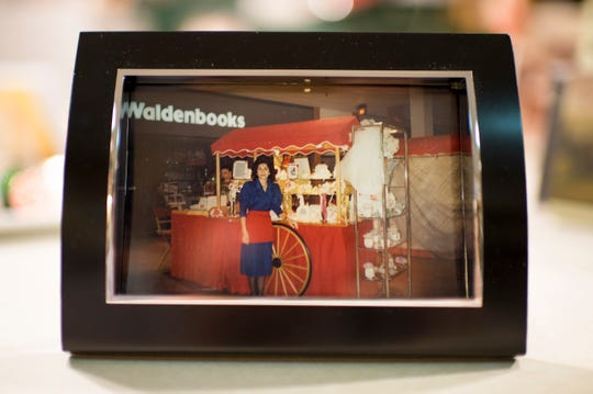 Celeste Cinalli displays a 1989 photograph in herself inside her Italian Treasures shop. Township officials are hoping to find a developer to revitalize the ailing mall.