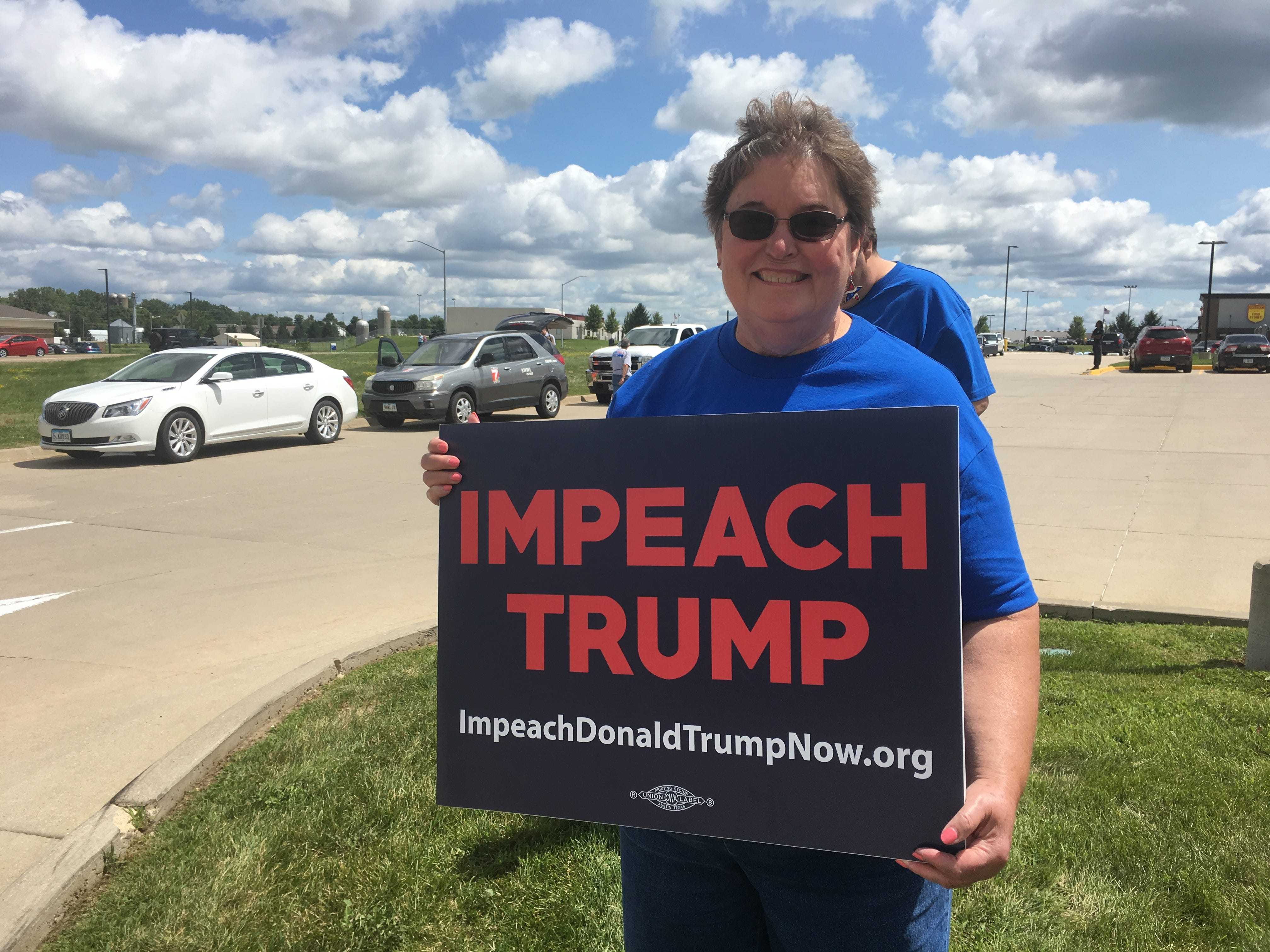 Kathy Geronzin, 70, of Maquoketa, a semi-retired teacher-librarian, demonstrates in Peosta Thursday, July 26, 2018 against President Donald Trump during his visit to Dubuque County.