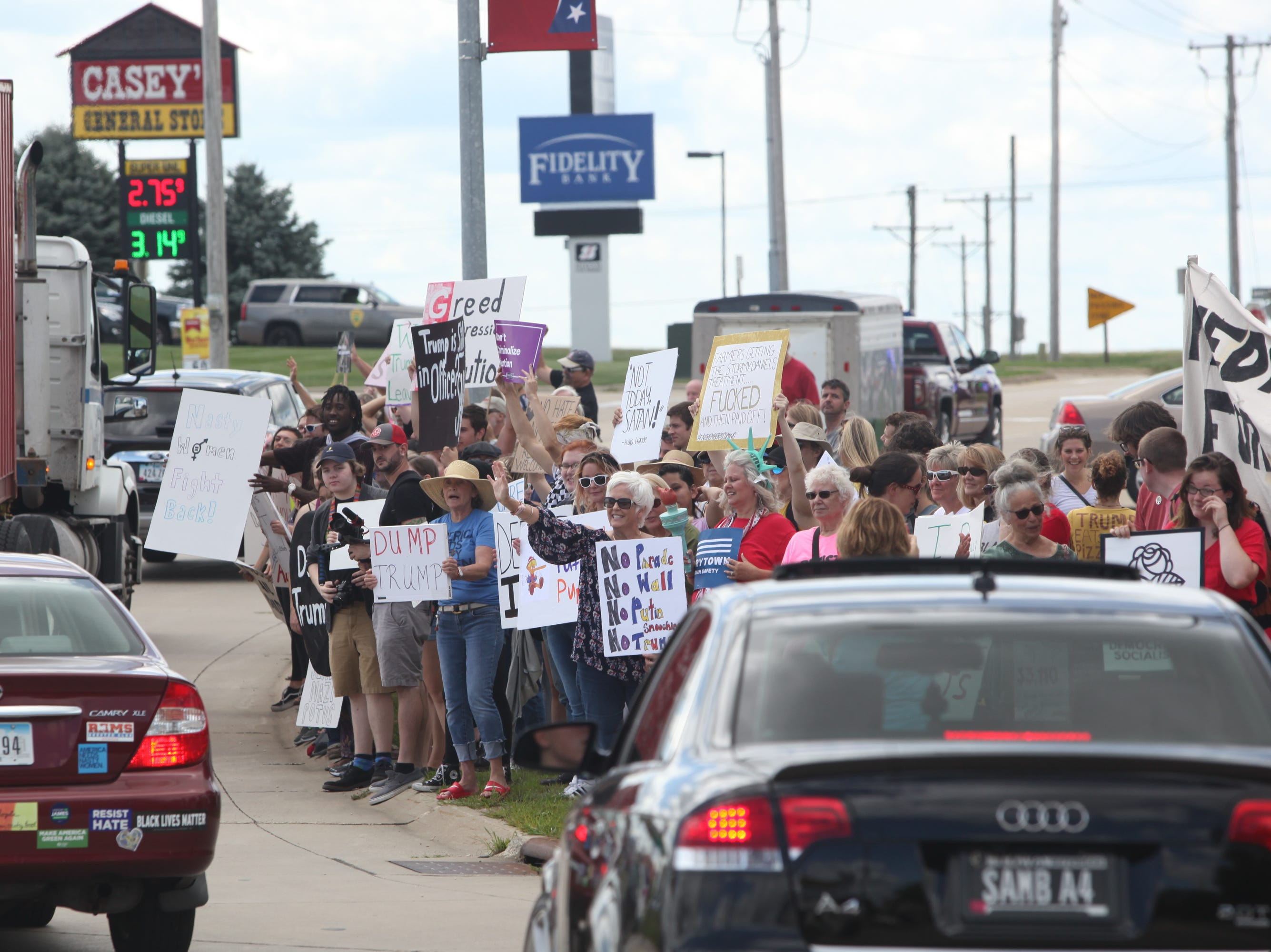 Demonstrators protest President Donald Trump's visit to Northeast Iowa Community College in Peosta, Iowa, on Thursday, July 26, 2018. Law enforcement officials estimated about 500 people gathered outside as Trump participated in a roundtable discussion about workforce development.