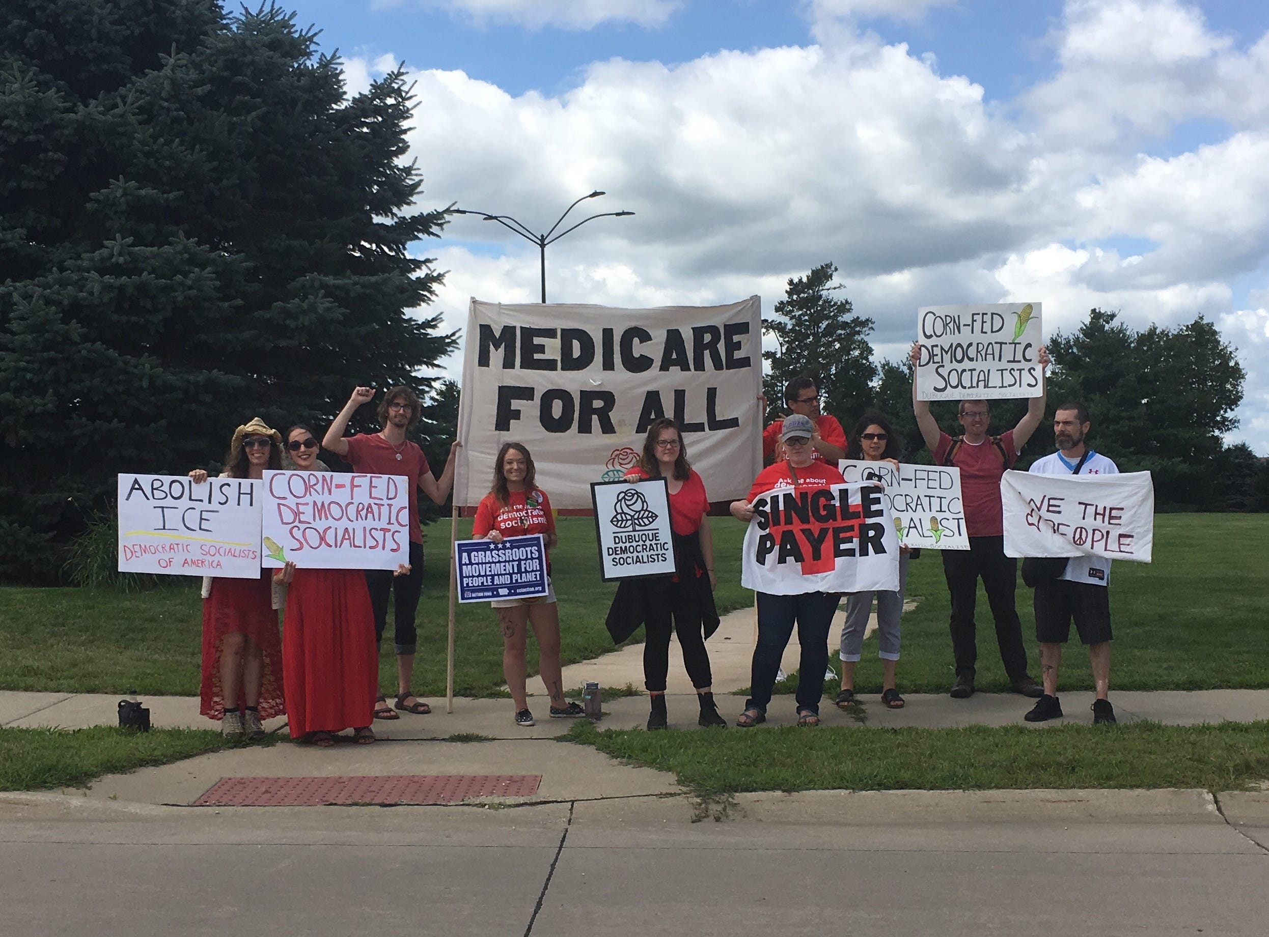 Protesters stand outside of Northeast Iowa Community College in Peosta, where President Donald Trump sat in for a roundtable discussion on workforce development with Iowa business leaders and educators, as well as Gov. Kim Reynolds and U.S. Rep. Rod Blum, R-Dubuque.