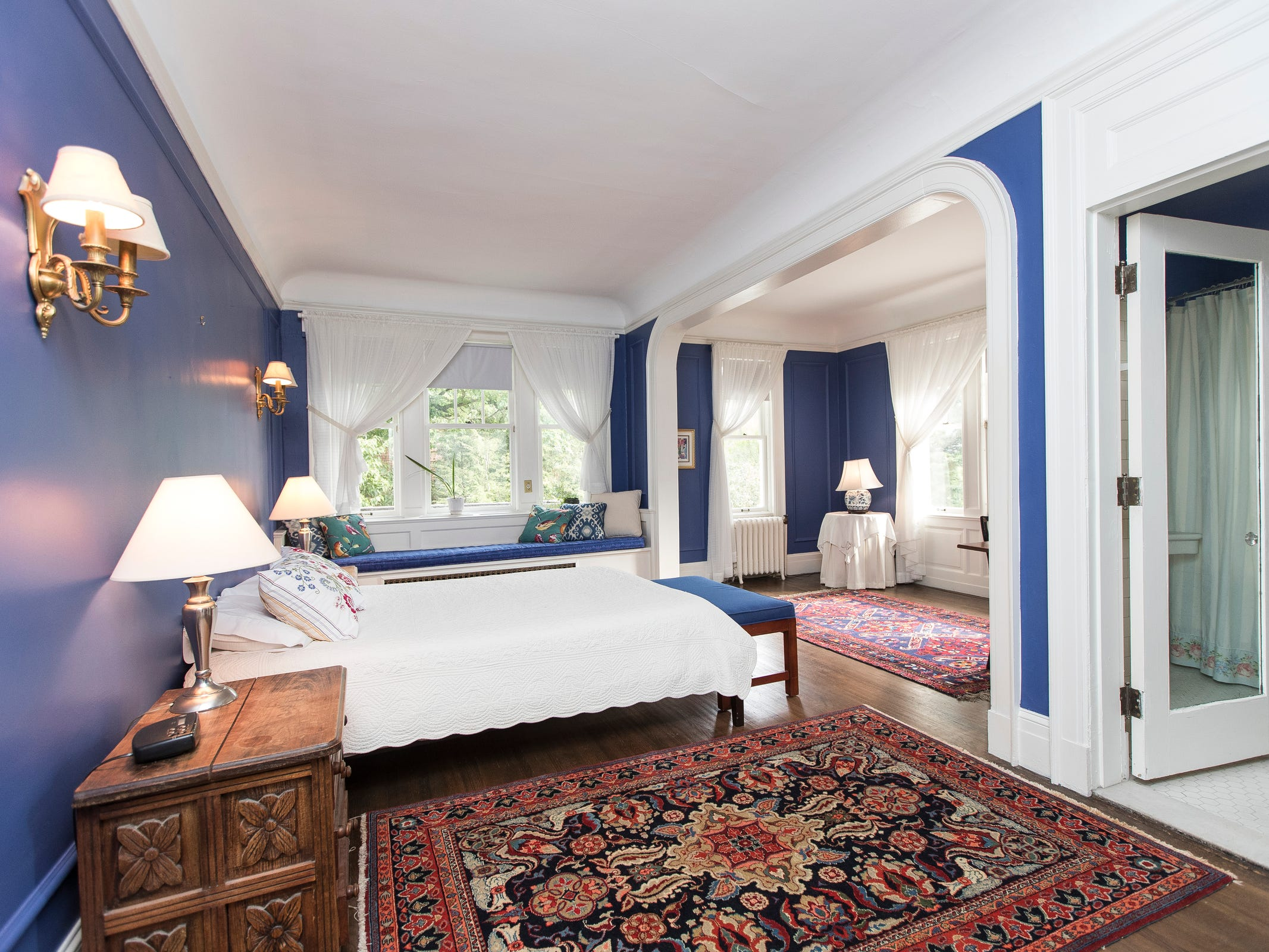 This guest suite with a sitting room and bath has blue-violet walls and glossy white trim.  these saturated colors, including Persian style rugs, give the interior the color punch of a David Hockney painting.