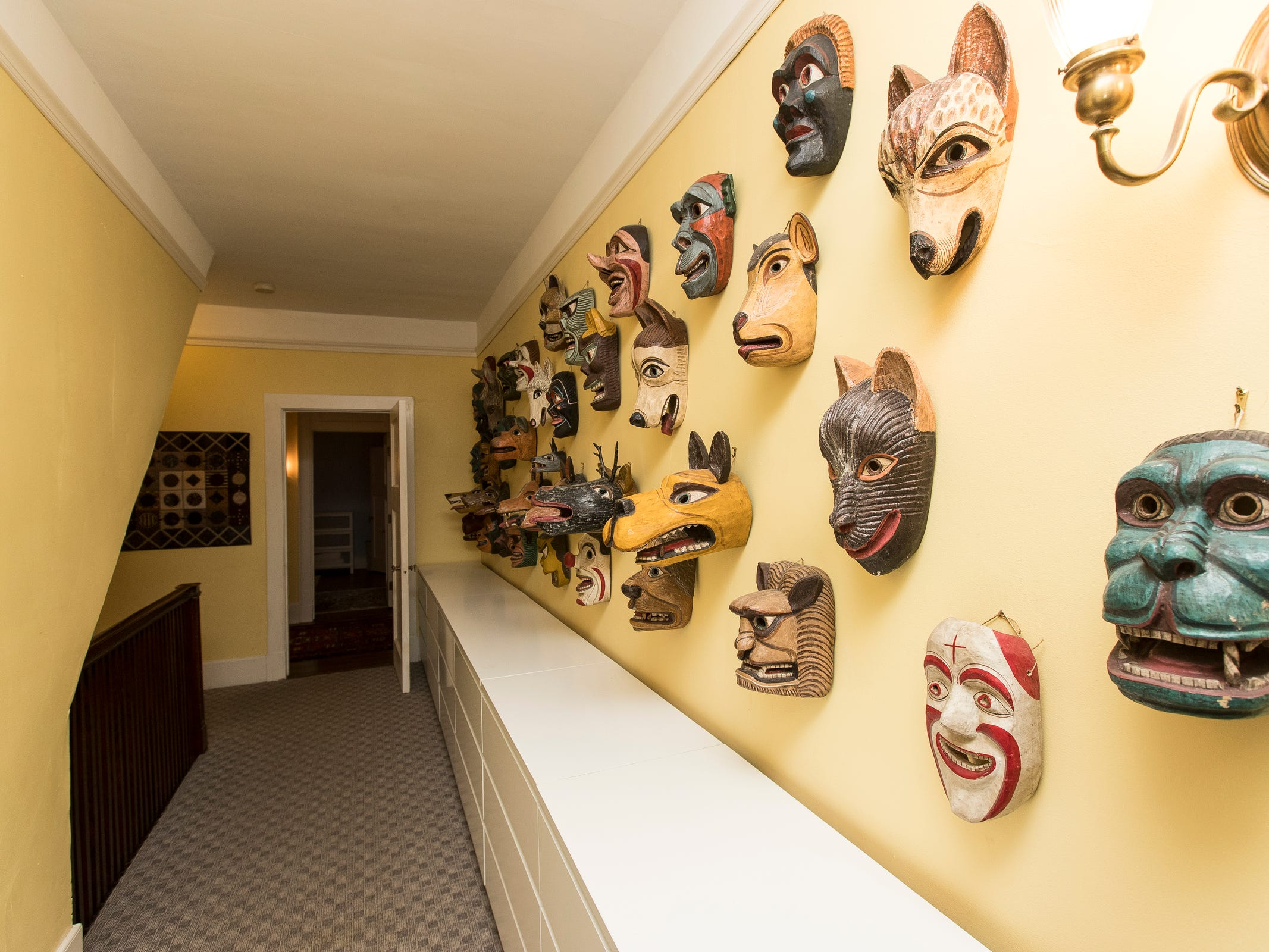 An upstairs hallway decorated with masks.