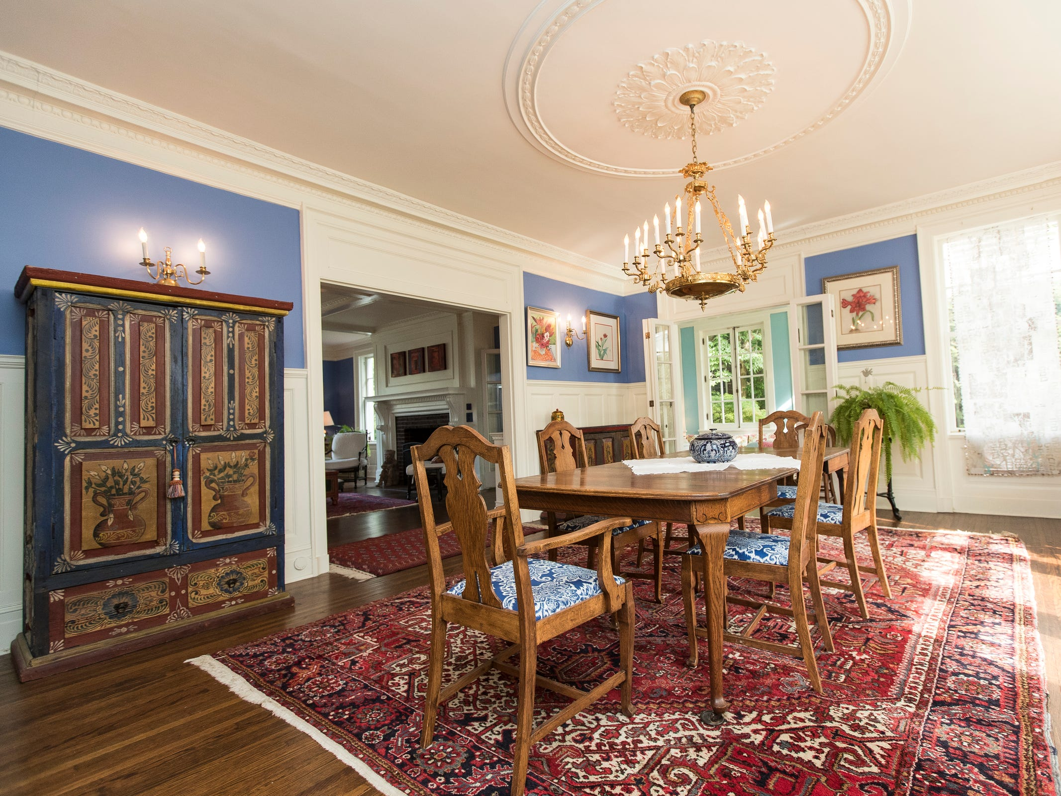 The party-sized dining room shows vivid colors with elaborate white woodwork and collections from around the world.