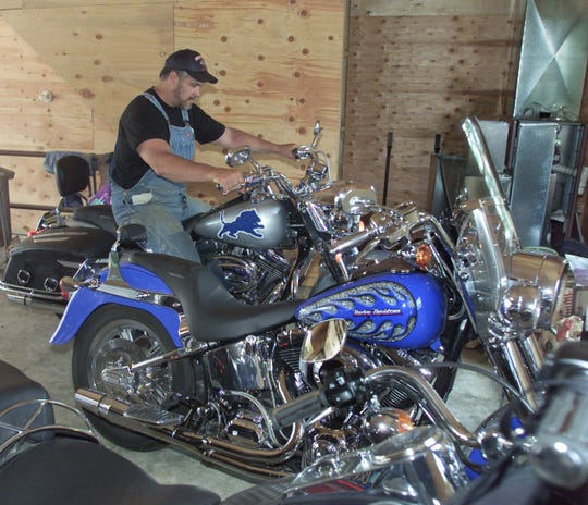 Lions president Matt Millen backs the newest of his four Harley Davidson motorcycles out of his garage at his  Pennsylvania home on July 11, 2001.