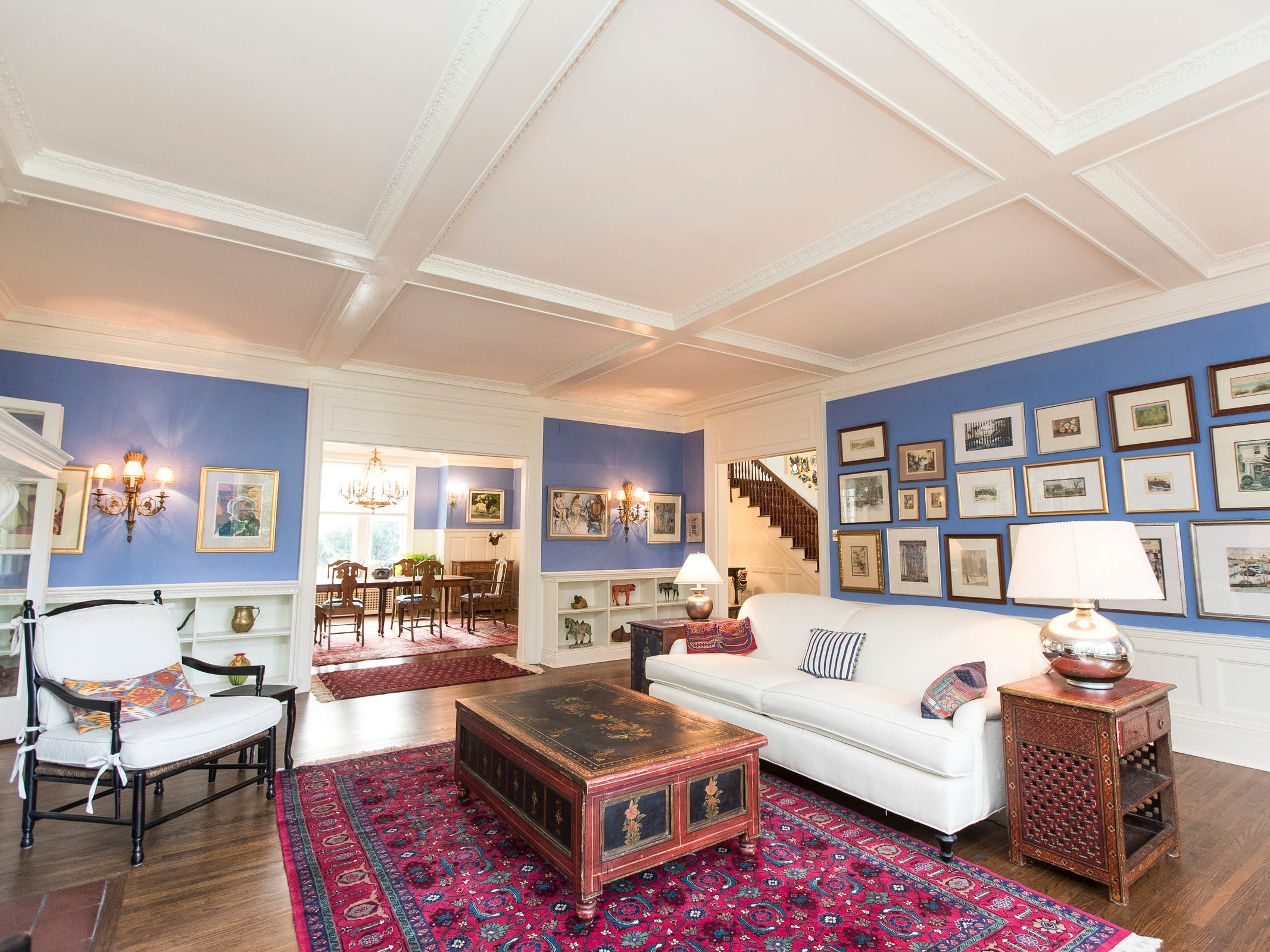 Massive Arts and Crafts woodwork is all painted glossy white and mixed with vivid colors like the lapis blue in the living room and the aquamarine in the sunroom behind. Many red-hued Persian style rugs add even more color pop