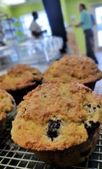 Idrissa Cisse assists customers at his East Side Bakery on Thursday, July 26. In the foreground are his big, hearty, not-too-sweet blueberry muffins.