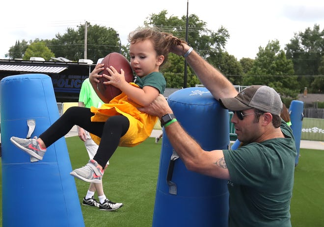 Ryan Fergot of Appleton lifts daughter Nora through the goal line on the Punt Return event during the Green Bay Packers Fan Experience at Lambeau Field Thursday, July 26, 2018 in Green Bay, Wis.