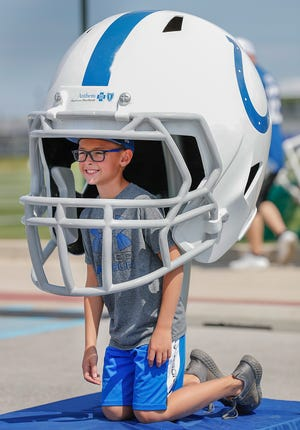 Carter Haag has his photo taken with a giant Colts helmet while visiting Colts City at Grand Park in Westfield on Thursday, July 26, 2018.