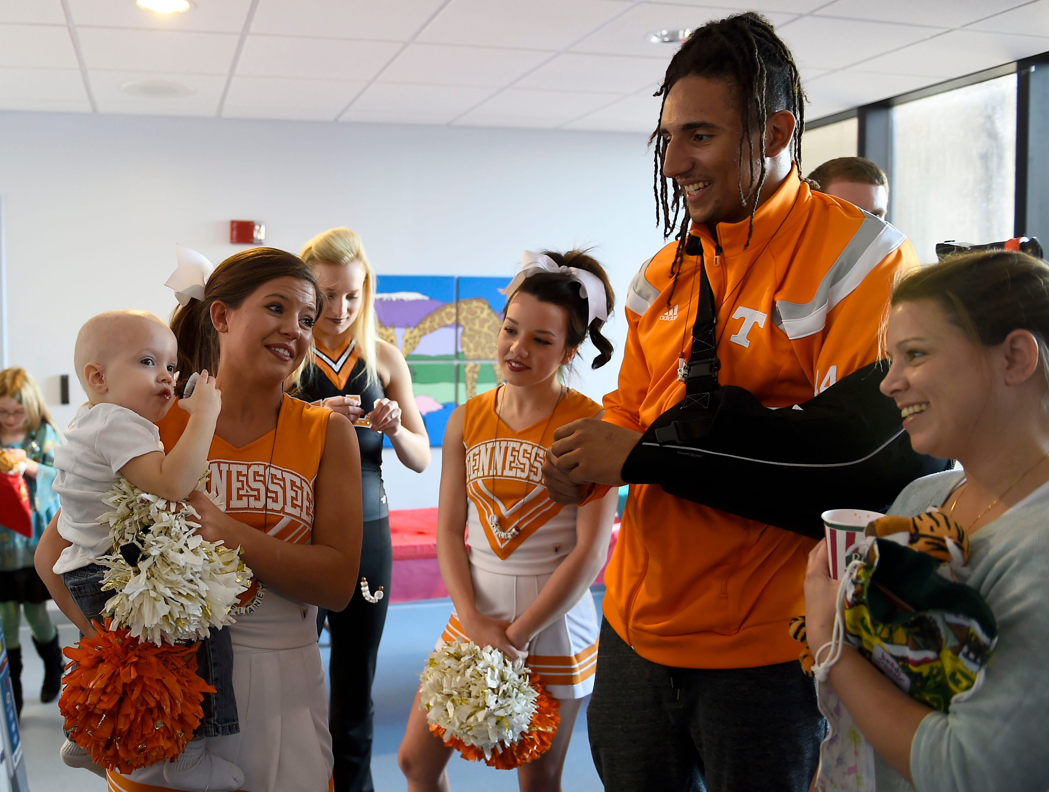 University of Tennessee cheerleaders Delaney Burton and Kylee Dick along with football player Jakob Johnson visit with patient Benny Andrews, 1, and his mother Joy Andrews, during a launch party for the Beads of Courage program at the East Tennessee Children's Hospital Wednesday, Jan. 28, 2015. Patients collect beads to serve as symbols of courage to honor and acknowledge each step of their treatment journey.