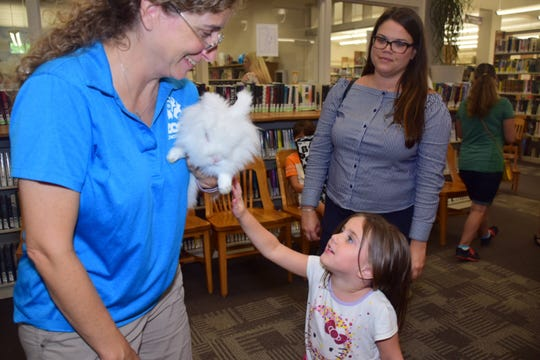 Kara Remington with Zoo Knoxville lets Peyton Bleimeyer, 4, pet B.B. the bunny while mom Ali Kolar looks on at Zoo Knoxville's Zoomobile Summer Reading Program on July 24.
