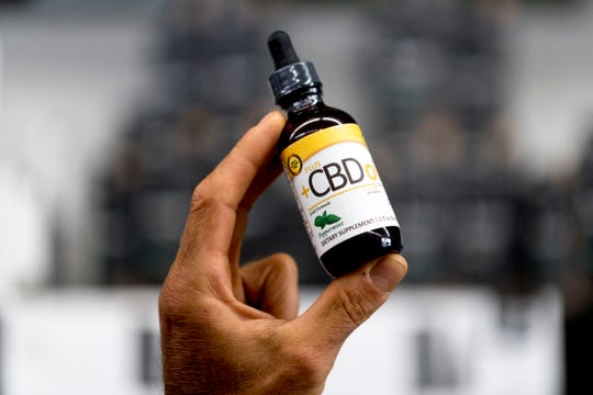 General Manager Mike Wright holds a bottle of CBD oil which is sold at Eddie's Health Shoppe in Suburban Plaza in West Knoxville, Tennessee on Thursday, July 26, 2018. CBD, one of 104 chemical compounds found in cannabis, has been gaining popularity recently for its pain and anxiety relieving properties