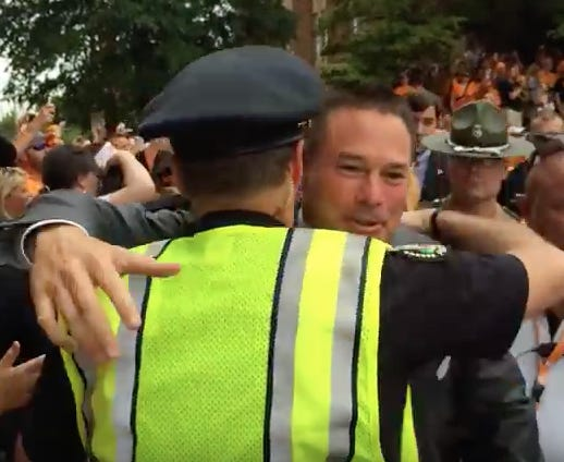 Former University of Tennessee football coach Butch Jones hugs former Knoxville Police Department Chief David Rausch during the Vol Walk before a game on Aug. 31, 2014.