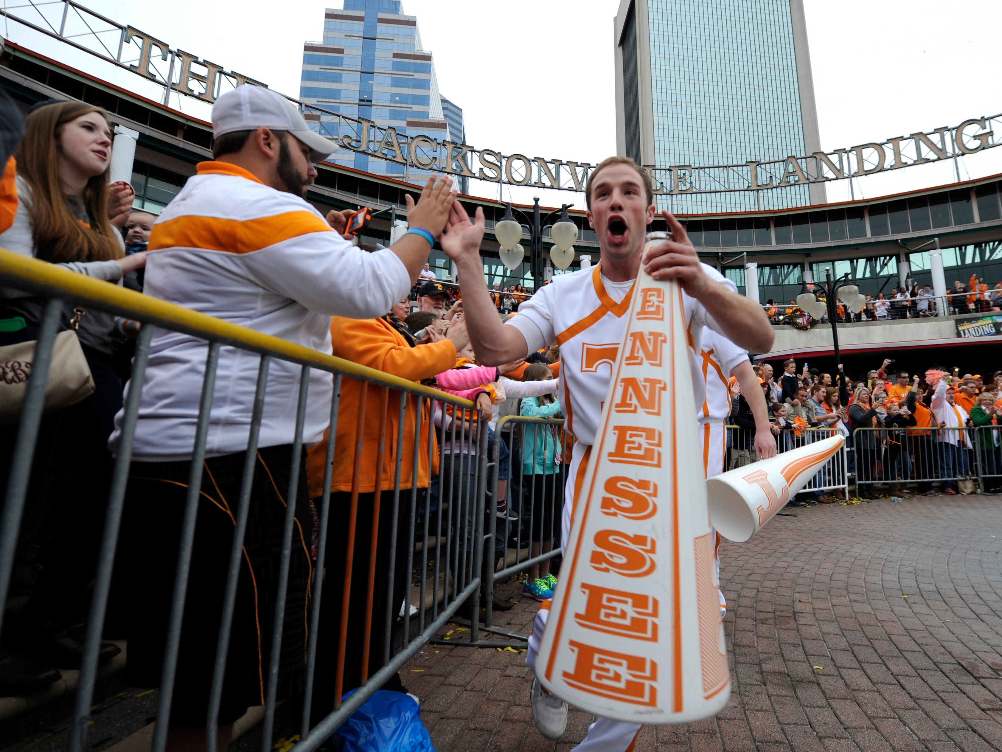 A Tennessee cheerleader high-fives fans during a pep rally at The Jacksonville Landing in Jacksonville, Fla. on Thursday, Jan. 1, 2015, before the next day's Taxslayer Bowl against Iowa.