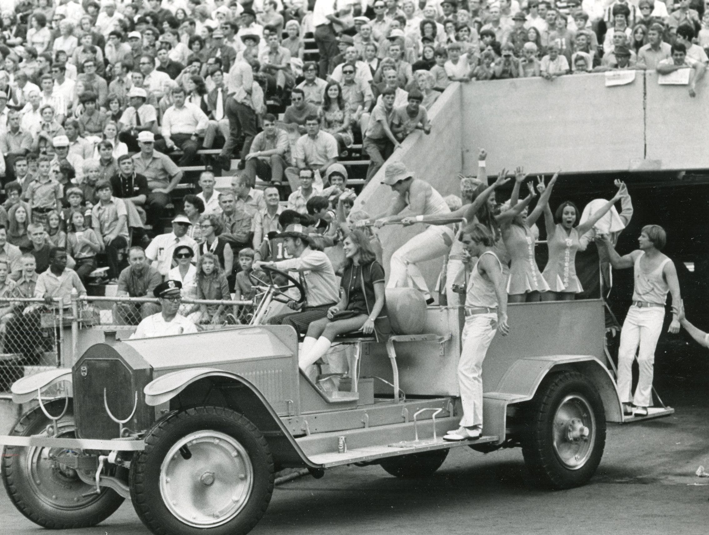 University of Tennessee cheerleaders arrive on the field in the Pi Kappa Alpha 1928 American La France Fire Truck, September, 1971.