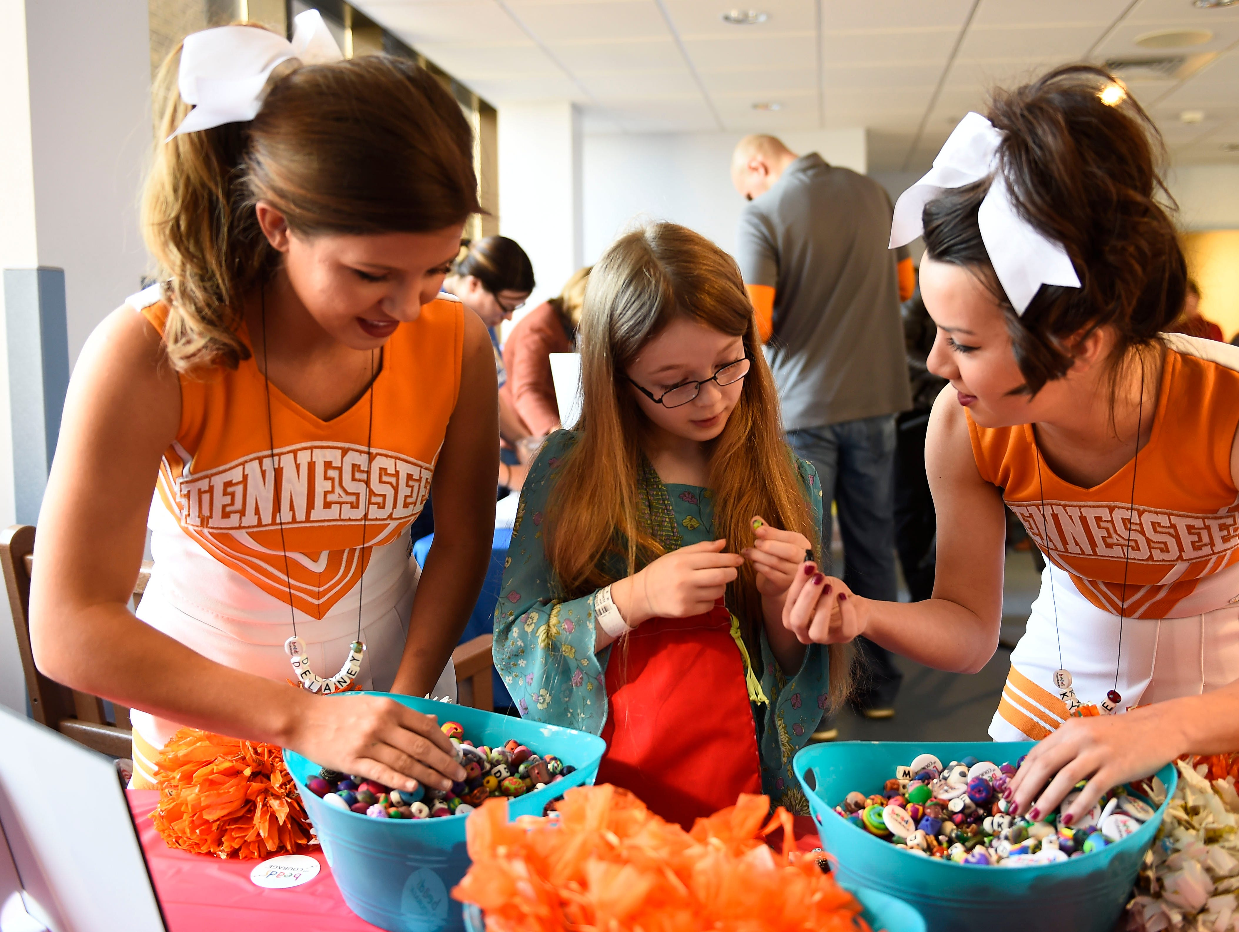 University of Tennessee cheerleaders Delaney Burton, left, and Kylee Dick, right, help patient Emilie Gregg choose beads during the launch for the Beads of Courage program at the East Tennessee Children's Hospital Wednesday, Jan. 28, 2015. Patients collect beads to serve as symbols of courage to honor and acknowledge each step of their treatment journey.