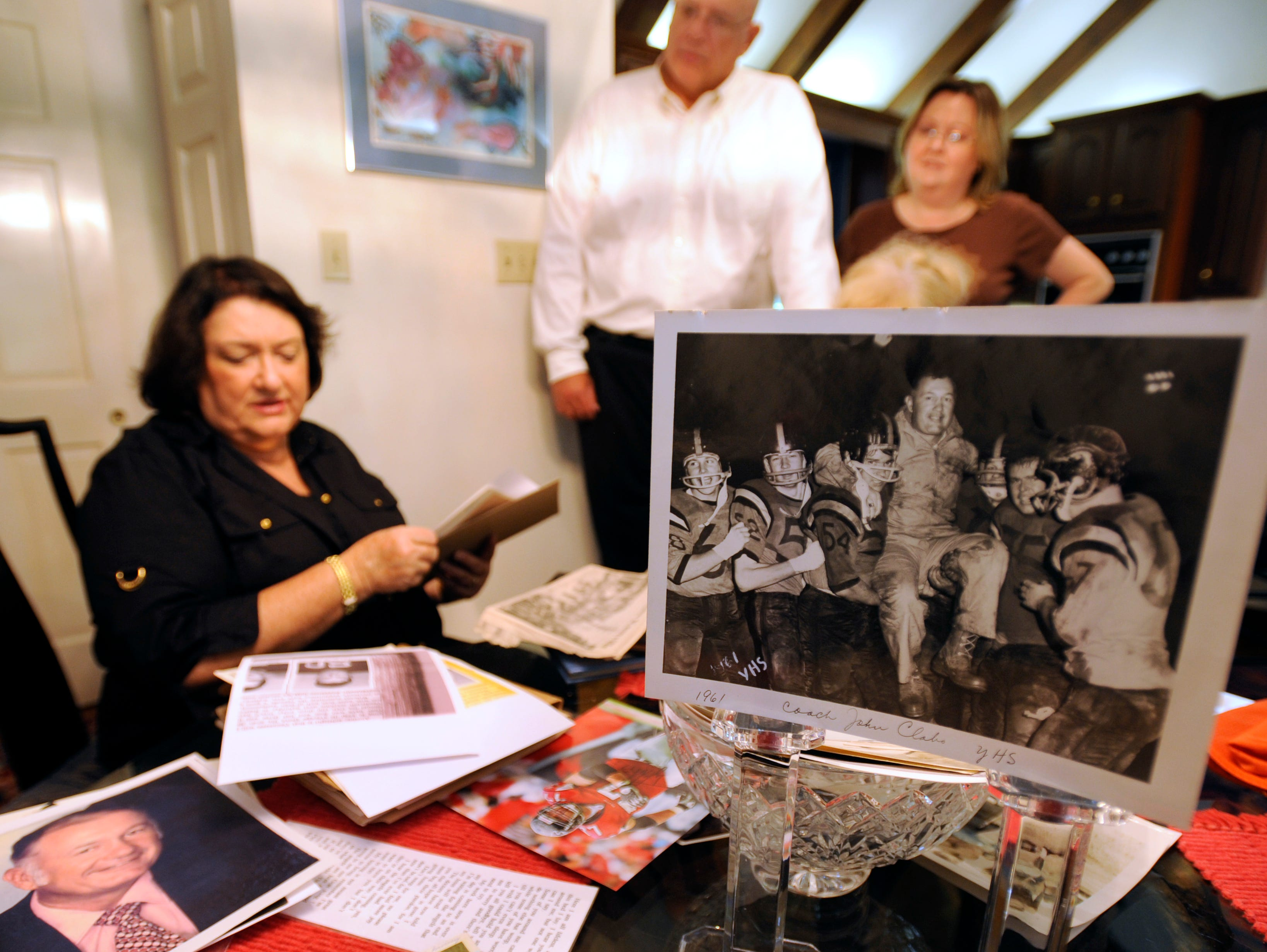 Linda Clabo Underwood, left, her brother Phil Clabo and her sister-in-law Tina Clabo sort through family photographs of their father Bill Clabo, who was a Young High School football coach for years.  Duff Park in South Knoxville was renamed in Clabo's honor.