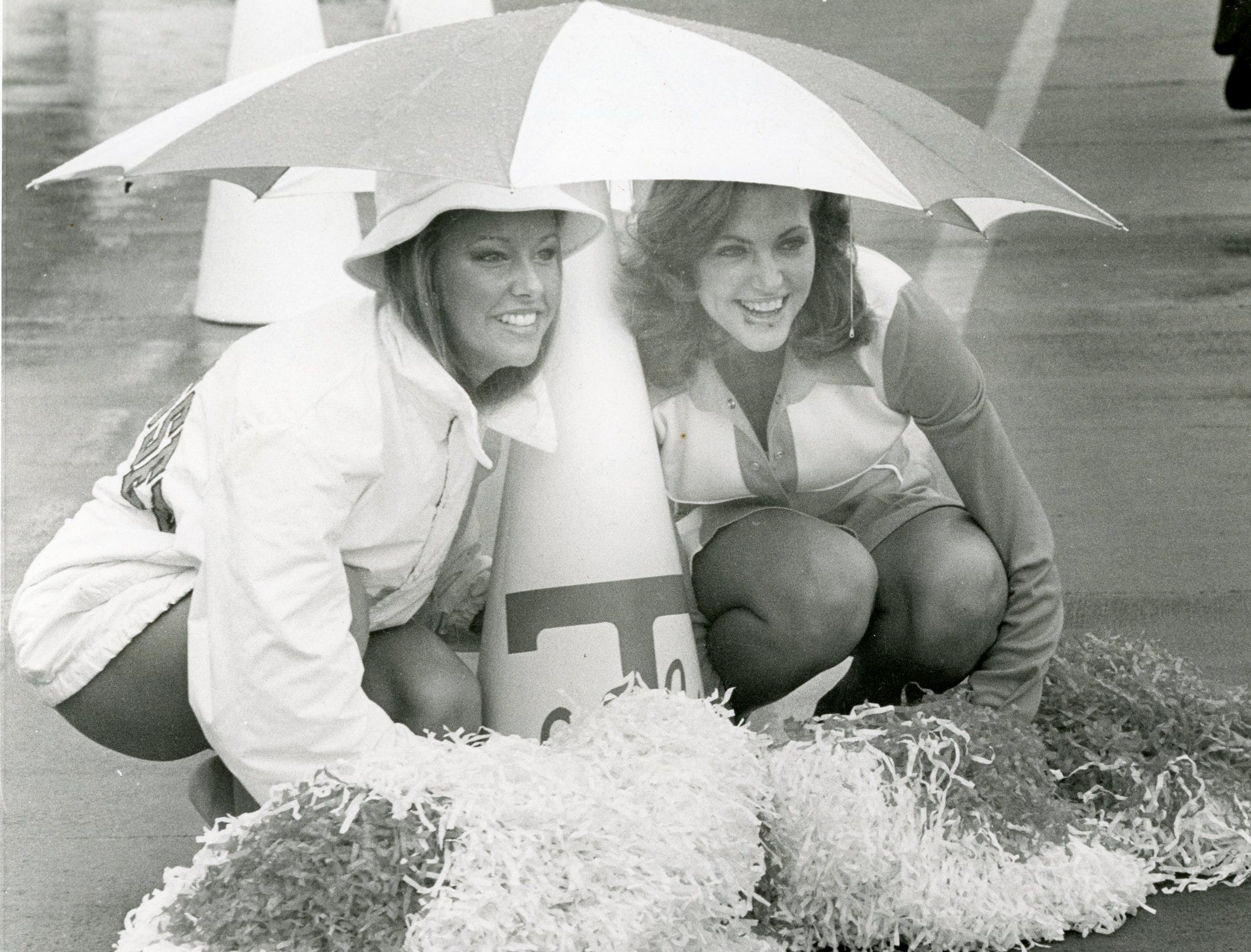 UT cheerleaders Pam Johnston and Candace Cullum shield themselves from the rain under an umbrella, October, 1977.
