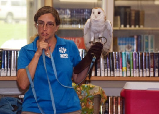 Kara Remington with Zoo Knoxville shushes the crowd while displaying Buckey the Barn Owl, who excited the crowd when he flapped his wings at the Zoomobile Summer Reading Program  July 24.