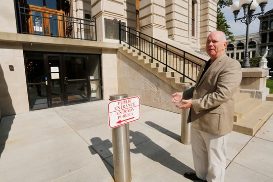 Former Tippecanoe County Sheriff and current county commissioner Tracy Brown talks about the bollard posts  Thursday, July 26, 2018, at the east entrance of the Tippecanoe County Courthouse. Twenty years ago, a truck loaded with explosives was driven through the doors of the east entrance in a failed attempt to blow up the courthouse. The person(s) responsible have never been caught.