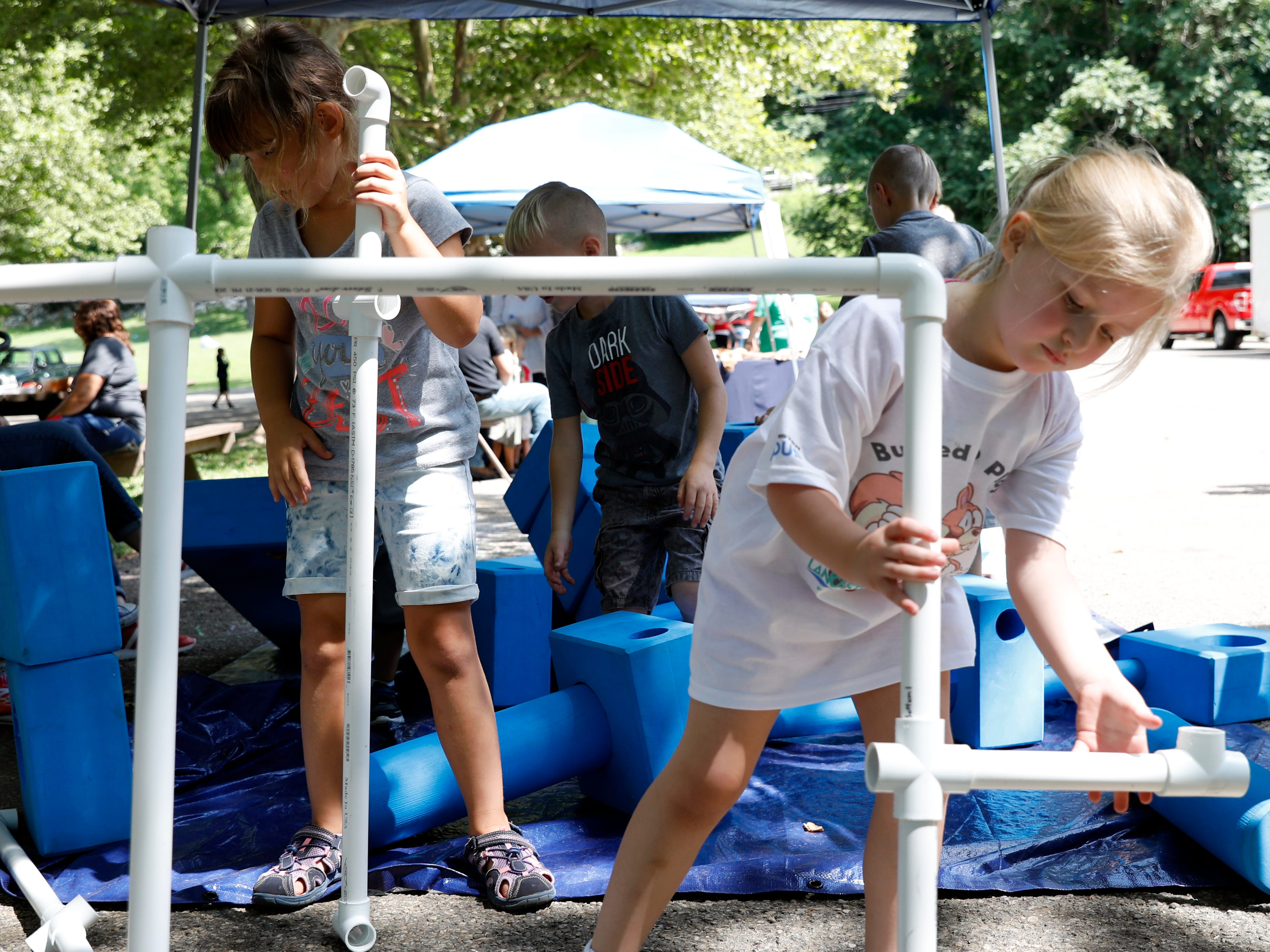 Vanessa Solt, 7, and Olivia Heston, 5, right, fit together pieces of plastic pipe Thursday, July 26, 2018, at Rising Park in Lancaster. Solt and Heston were playing at the AHA! Children's Museum tent during the Lancaster Festival's Rising Park Day.