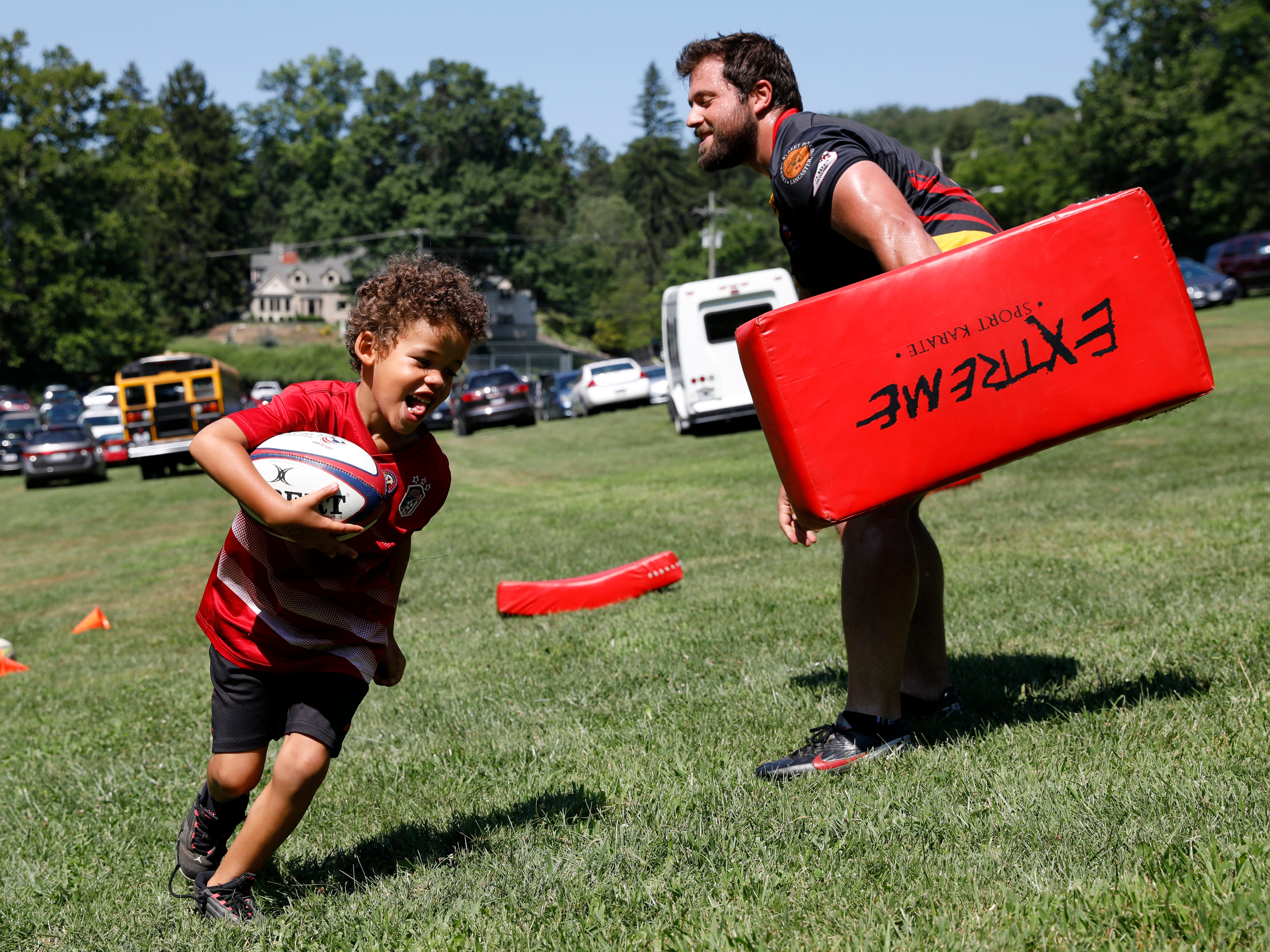 Mahkye Gamble, 7, runs past Rafael Lisboa after pushing him back to pick up the rugby ball Thursday, July 26, 2018, at Rising Park in Lancaster. Lisboa and other members of the Lancaster Men of Stone Rugby Club were teaching children basic rugby skills at the Lancaster Festival Rising Park Day.