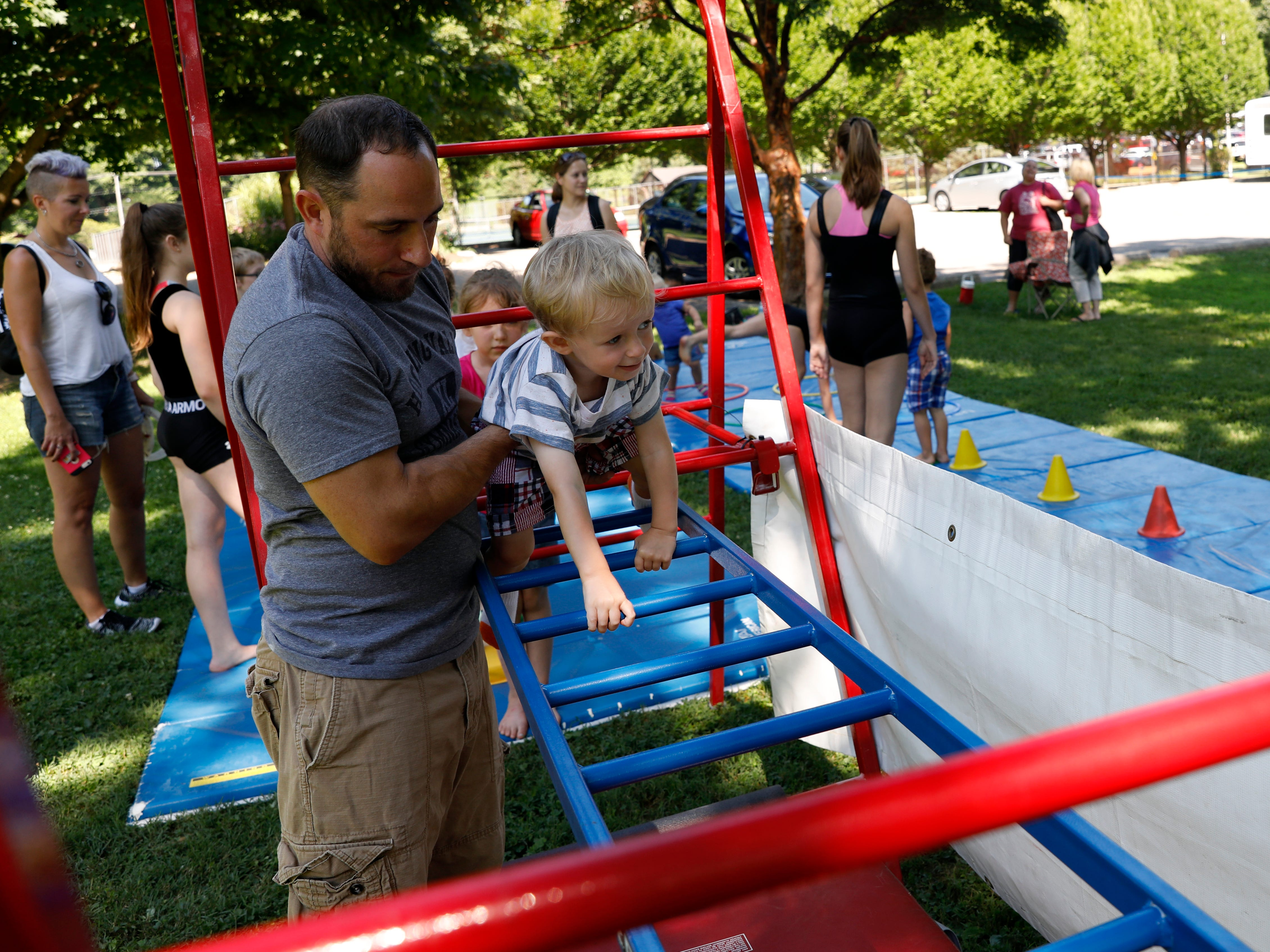 Maddox Wood, 1, crawls across a ladder with the help of Dick Huntwork, from Hocking Valley Youth Sports Center, Thursday, July 26, 2018, at Rising Park in Lancaster. Hundreds of children came to the park to experience Rising Park Day as part of the Lancaster Festival.