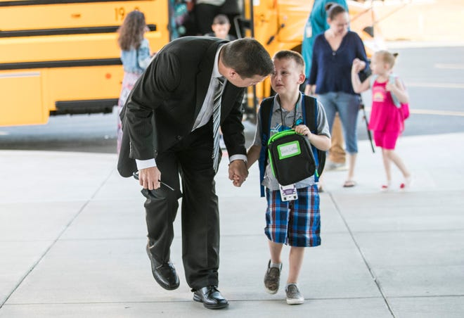 Green Valley Elementary school principal Brian Kehrer comforts a scared Noah Luther as the two walk towards the school's entrance on the first day of class Thursday morning. July 26, 2018