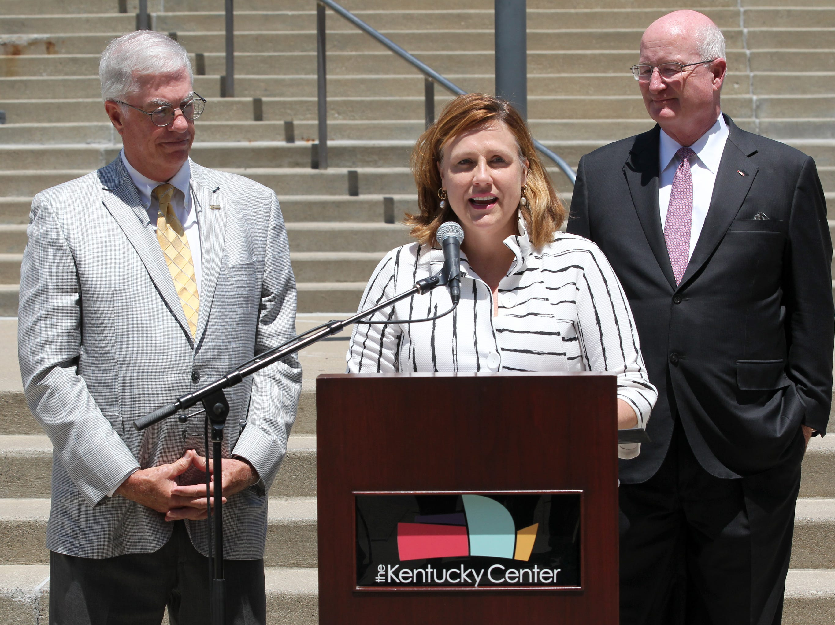 Kentucky Center President Kim Baker addresses the crowd during a press conference at the Kentucky Center for the  Arts as the center's Chairman Bruce Ferguson (left) and Kentucky Secretary of Finance and Administration William Landrum look on in Louisville, Kentucky.    July 26, 2018