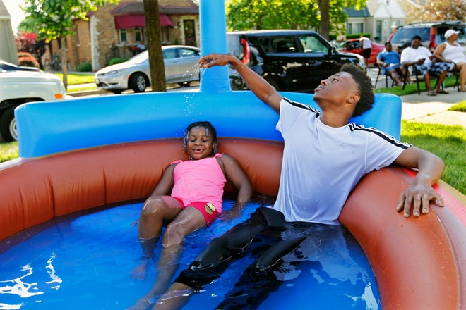 Donovin Harris, 19, right, hangs out in the kiddie pool with his niece, Kastacia, 7, at their Milwaukee home on June 17, 2018.