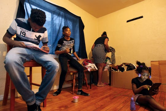 Shana Sykes (center) sorts through boxes of packed clothes  while her children Kravon Wilson Jr., 13, Shnya Sykes, 11, and Zatavia Burks-Sykes, 3, sit in the living room of their rental home on Feb. 5, 2018.