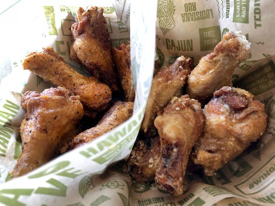 Wing Stop customers favorite, Lousiana Rub, left, and our pick, Garlic Parmesa, right, The menu says, Lousiana Rub: Cajun creation, A crispy dry rub, a hint of garlic, some Deep South Cajun love and you've got a wing that's simply addictive. Meal for 2; With bone-in choice 15 wins 2 favores 2 dips,  $20.99. National Chicken Wing Day is July 29, so where can you find great wings in Collier and south Lee counties?The photo was taken in Naples, FL. Tuesday  July 14, 2018.