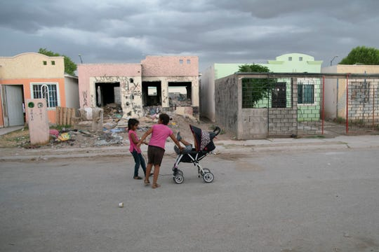 Children pushing a stroller in the street in front of Adrián Hernández's home in Juárez, Mexico.
