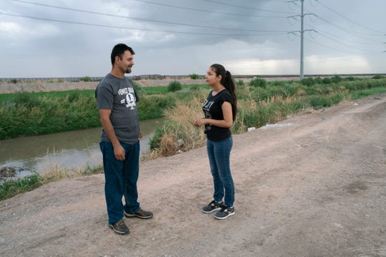 Adrián Hernández with his daughter, April, near his home in Juárez, Mexico, by the border fence.