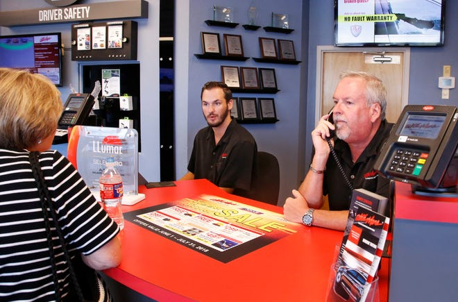 Greg Goodman, right, assists a customer on the phone while son Chandler Goodman, center, helps a customer at the counter, in their Alta Mere franchise in Oklahoma City.