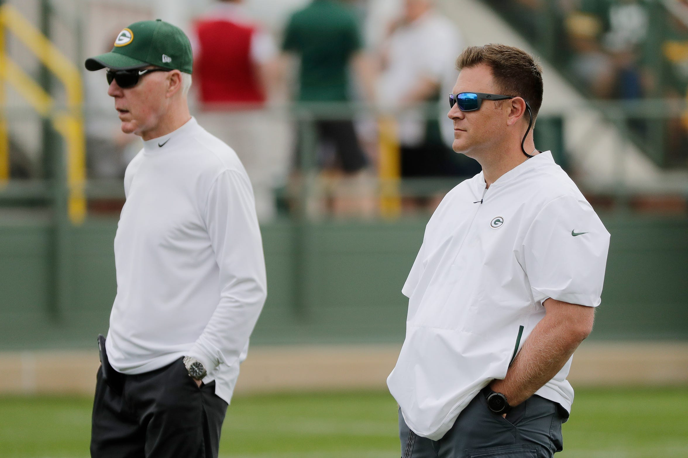Packers GM Brian Gutekunst (right) and former GM Ted Thompson watch training camp practice at Ray Nitschke Field on Thursday, July 26, 2018 in Ashwaubenon, Wis.
