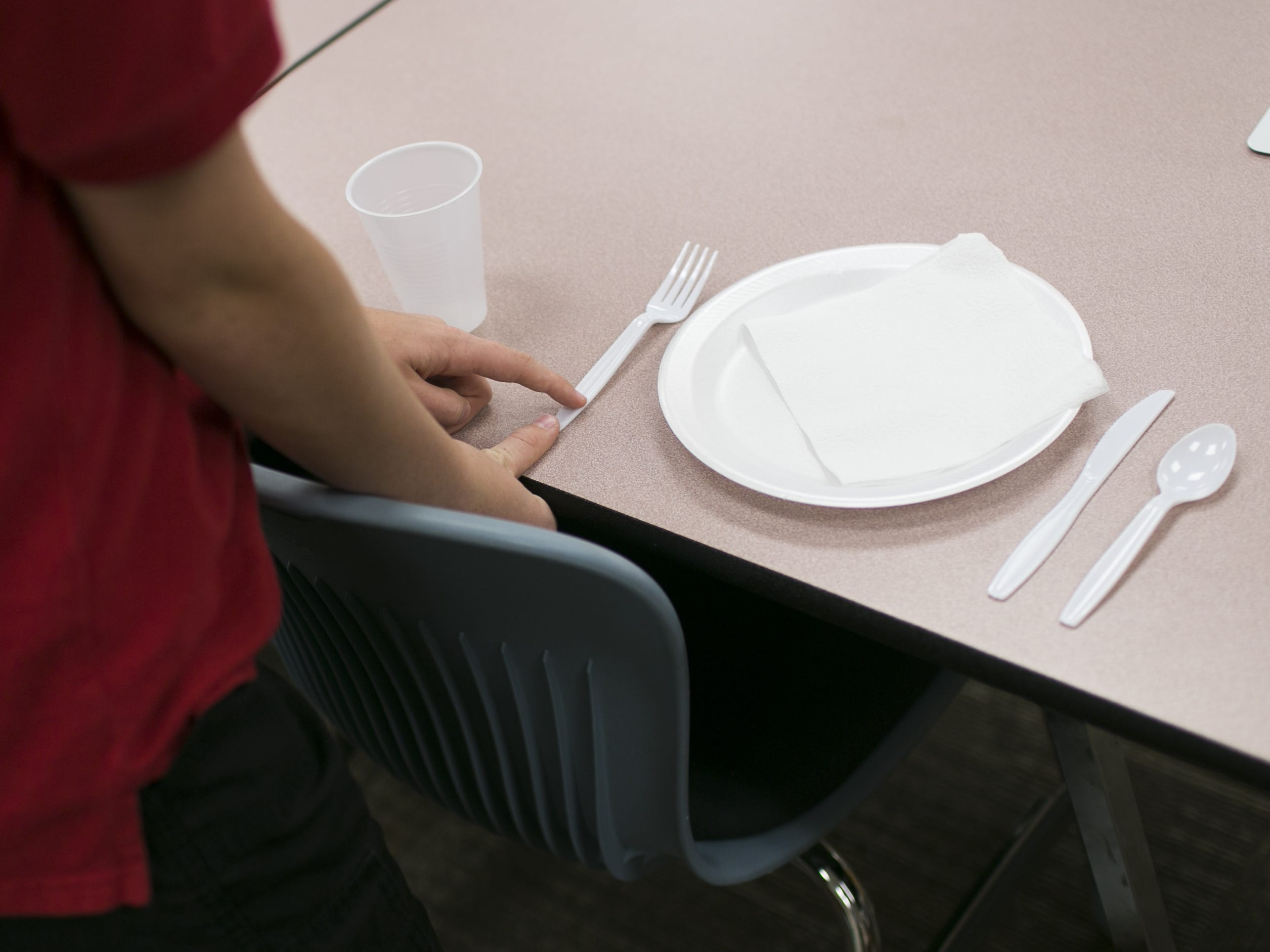 A student in the class moves his silverware an inch from the table's edge during an exercise in Scottsdale on July 20, 2018.  SueAnn Brown started the  program with the aim to teach kids, adults and companies on proper manners and social etiquette.