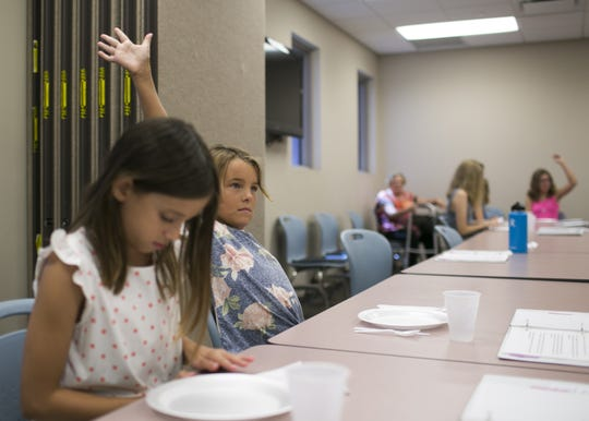 Rachael Ingram, 9, raises her hand to answer a question in class on July 20, 2018. SueAnn Brown started the program with the aim to teach kids, adults and companies on proper manners and social etiquette.