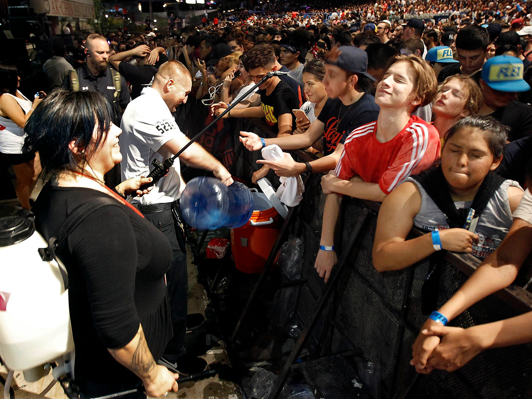 Security staff offer water and use a sprayer to give fans some relief from the heat during Logic's Bobby Tarantino vs Everybody Tour at Ak-Chin Pavilion in Phoenix on Wednesday, July 25, 2018.