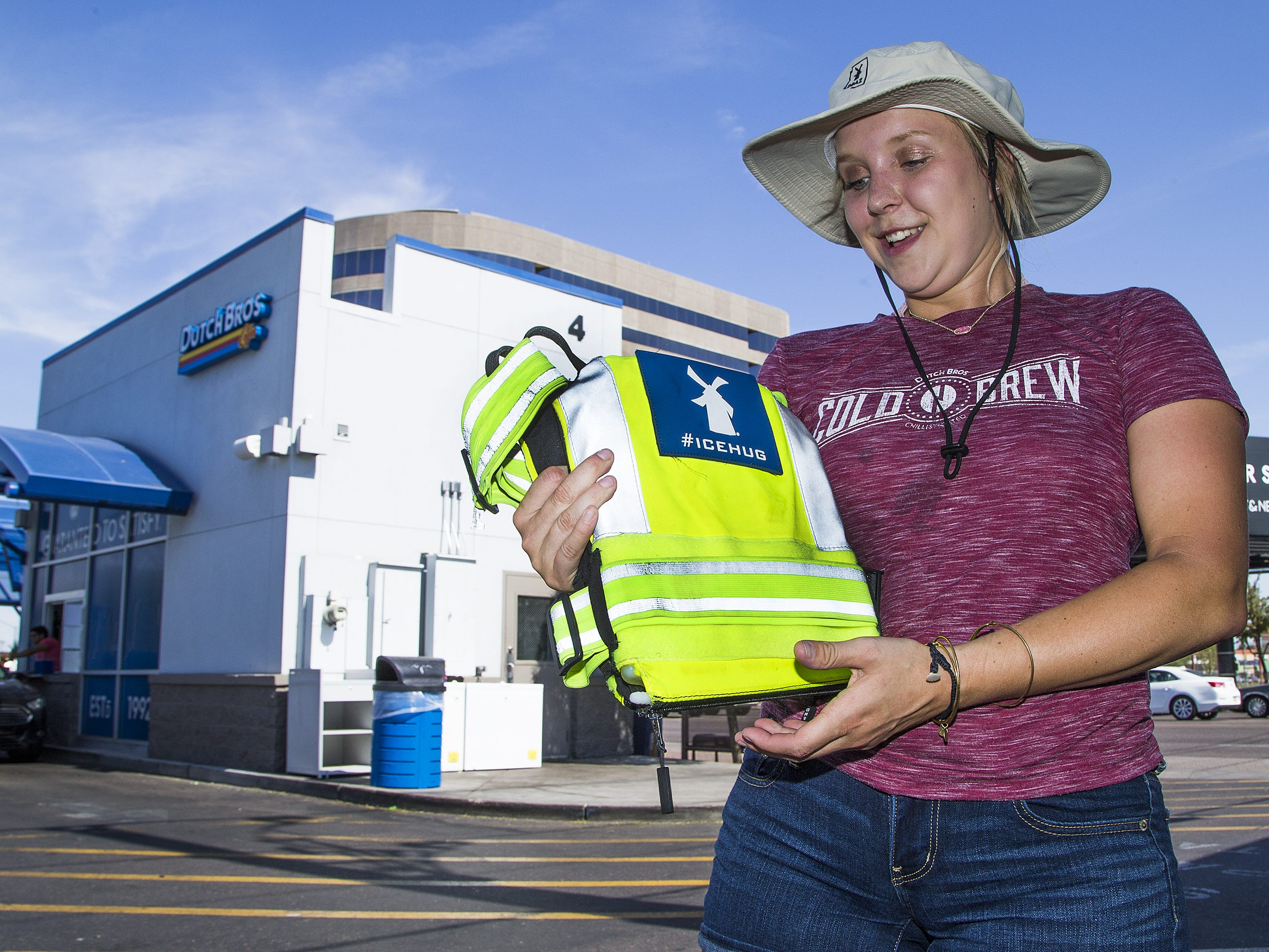 Dutch Bros. manager Allie Wilson shows off the Ice Hugs cooling vest at the Camelback Road and Central Avenue store in Phoenix on July 25, 2018. The company has started using the vests to cool down their workers who take orders outside in the blazing heat in Phoenix.